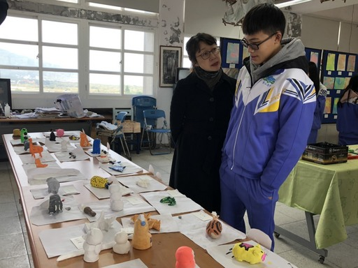 華梵大學美術與文創學系聶蕙雲副主任(左)與金山高中學生討論作品。