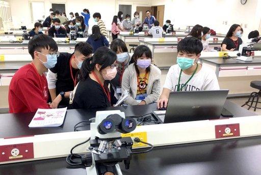 輔導員藉由顯微鏡組織切片,向高中生介紹人體各器官的組織結構。(義守大學提供)