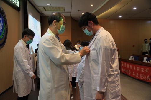 元培醫技系主任陳有任(左)等師長一一為即將進入醫院實習的學生授袍