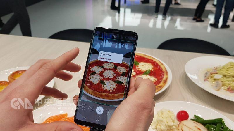 用手機鏡頭就能即時翻譯、拍攝物品進行比價、甚至判斷食物卡路里,今年MWC展上,AI(人工智慧)再度成為手機決勝戰場,並提升擴增實境(AR)體驗。圖為三星S9搭載的Bixby新功能。中央社記者江明晏攝 107年2月27日