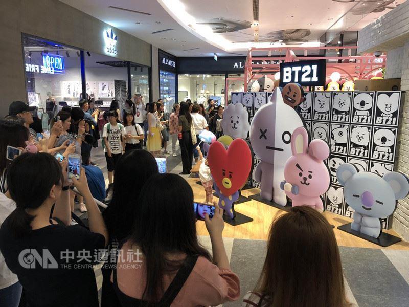 全球角色品牌LINE FRIENDS宣布,與韓國男團BTS防彈少年團攜手設計的宇宙明星BT21系列商品,5日在LINE FRIENDS Cafe & Store台北新光三越開賣,粉絲們排隊進場與現場看板合影。中央社記者吳家豪攝 107年7月5日