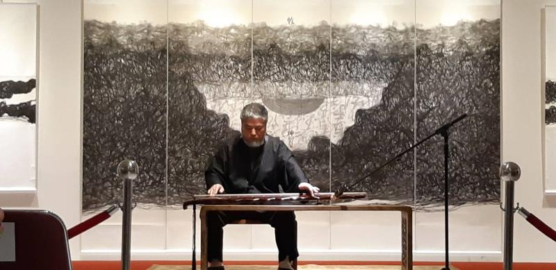 :寶吉祥藝術中心於國父紀念館舉行《線之道,樊洲水墨世界巡展》,樊洲大師於開幕式彈琴,背後為其作品