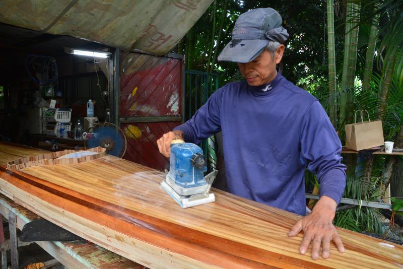正在製作的獨木舟,以船首至船尾的柳安木為中心,夾雜著香杉、梧桐、黃檜、肖楠等不同顏色或材質的拼接木材,往兩側船舷延伸線條,呈現美麗的弧線。