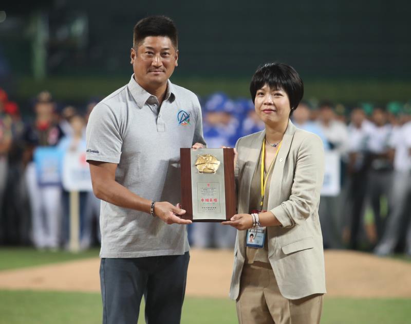 劉柏君(右)10月在洲際棒球場,亞洲棒球錦標賽開幕式中,接獲棒協理事長辜仲諒(左)頒發獎座,勉勵她為棒球的努力。