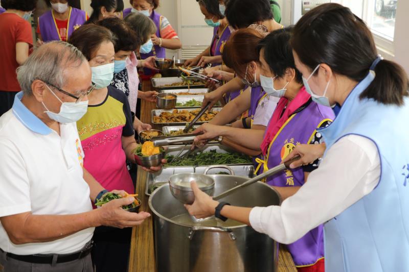 畫眉鳥晚香玉協會志工團幫長輩打餐  洪佳君議員也幫忙舀湯。