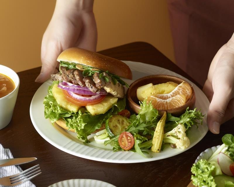 好丘一口氣新推出超過30款新餐點!貝果堡新菜「桔香鹹豬肉貝果堡」,以香料馬告自製鹹豬肉,辛暖香麻的風味搭配多種蔬果,交疊出多層次口感和齒頰留香的滋味.(圖/好丘提供)