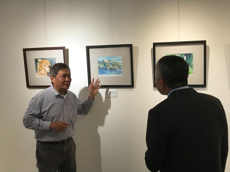 王正明於畫展會場,仔細解說每幅畫作背後的有趣故事。