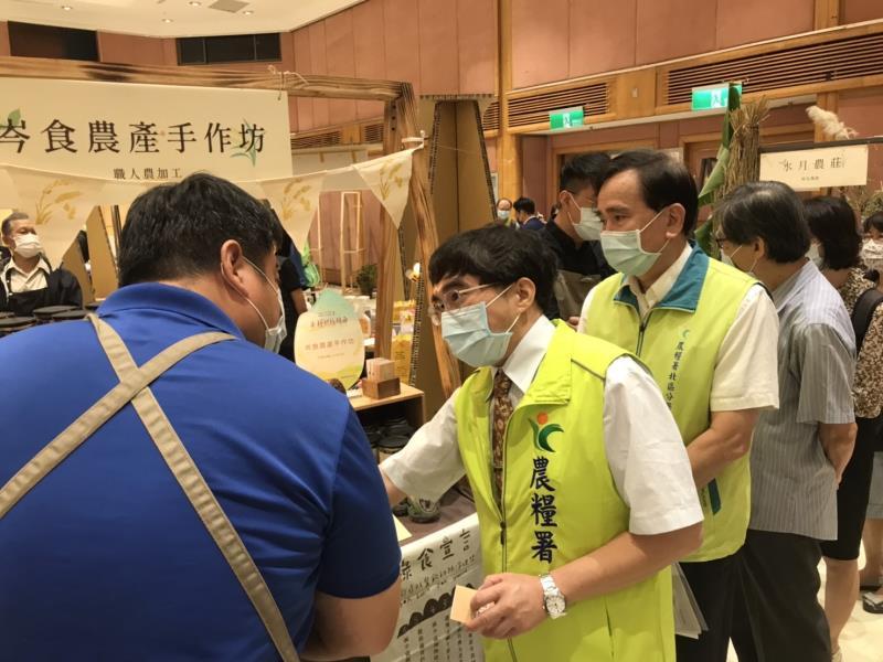 農糧署主秘陳啓榮(左二),在展場中與農民互動交流。
